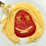 A pasta dish with a smiley face